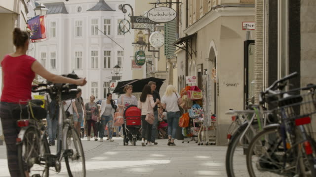 Wide slow motion shot of people in busy city / Salzburg, Austria
