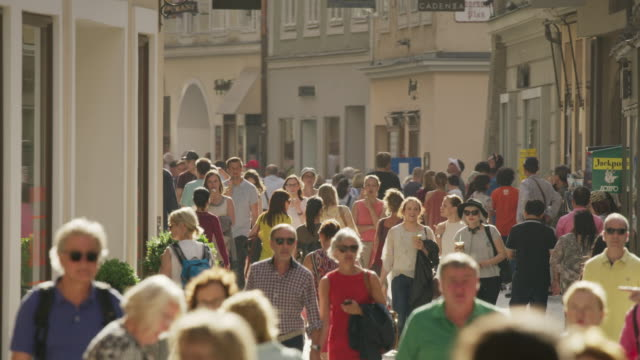 Wide slow motion shot of people walking in busy city / Salzburg, Austria