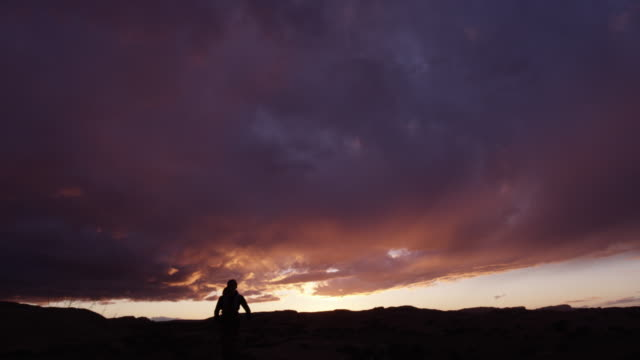 Wide slow motion shot of silhouette of woman running in desert / Moab, Utah, United States