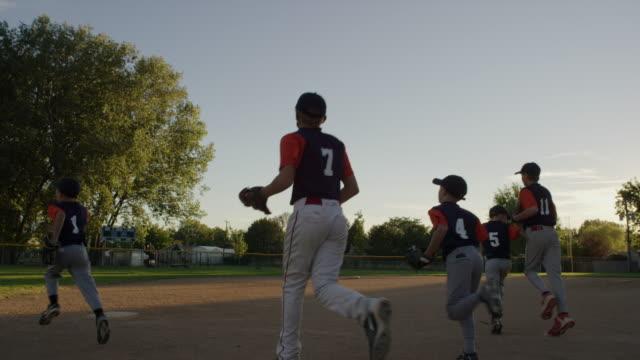 Wide slow motion shot of team running on baseball field / American Fork, Utah, United States