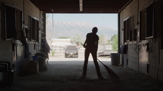 Wide slow motion silhouette of girl cleaning floor of stable / Lehi, Utah, United States