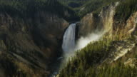 Wide slow motion view of waterfall in forest / Wyoming, United States