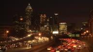 Wide, static, timelapse shot of traffic flowing below the lit up Atlanta Skyline.