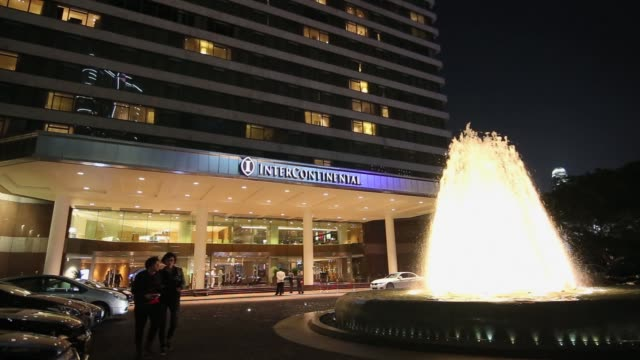 Wide tilt top to bottom shot The InterContinental Hotel stands illuminated at night Hong Kong China on Thursday Jan 29 2015 Medium shot The entrance...
