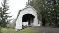 Wide tilt up on white covered bridge with evergreen trees in background.
