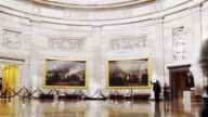 A wide time lapse shot of the interior of an art museum as visitors pass by paintings in Washington DC