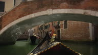 Wide tracking shot of gondoliers with tourists in urban canal / Venice, Italy