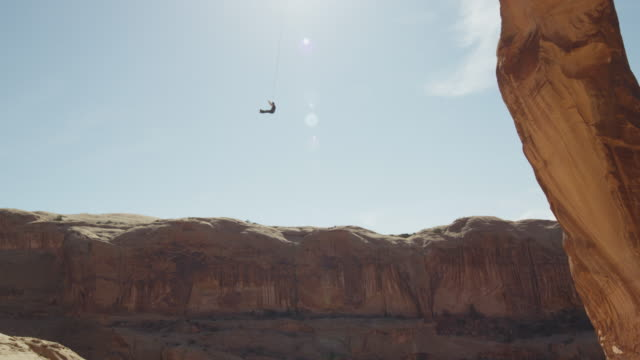 Wide tracking shot of man swinging from arch on rope / Corona Arch, Moab, Utah, United States