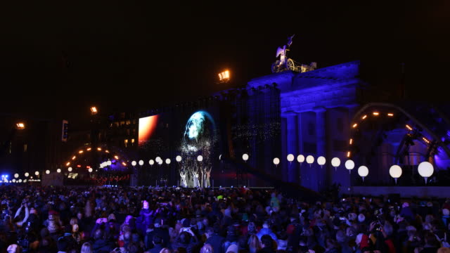 Wide view of a dance performance of a group dressed in white interacting with the planet projected on big screen at the back of the Brandenburg Gate...