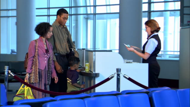 Wide view of a family checking their tickets with the flight attendant at the gate.