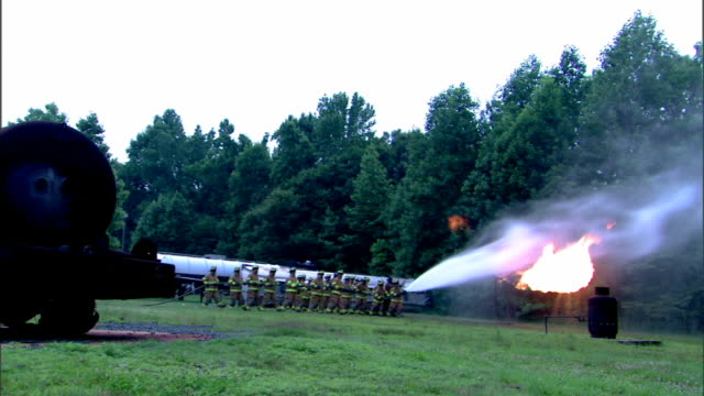 Wide view of firefighters working to control a fire from a broken liquid propane pipe