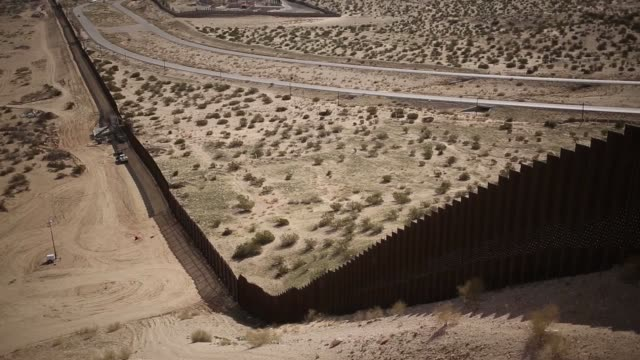 Wide views of the Southern border fence of the United States in Sunland Park US on Friday Feb 17 2017 Shots wide shot of tire treads in the sand near...