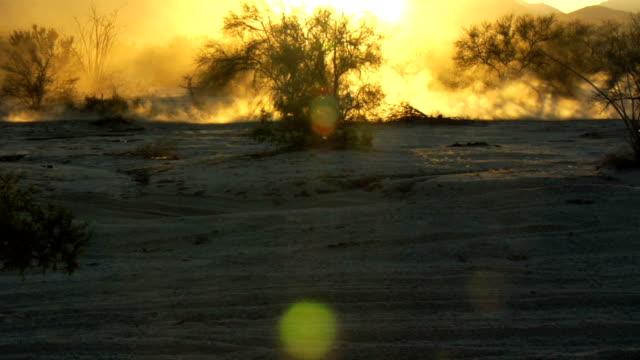 Wideshot of  motocross back lit dust