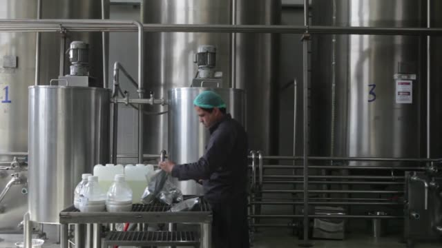 Wideshots of the bottling machine at work while employees monitor the process at Habib Gulzar NonAlcoholic Beverage Limited the Coca Cola bottler in...