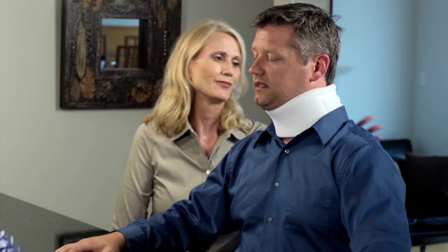 Wife Comforts Injured Husband in Neck brace