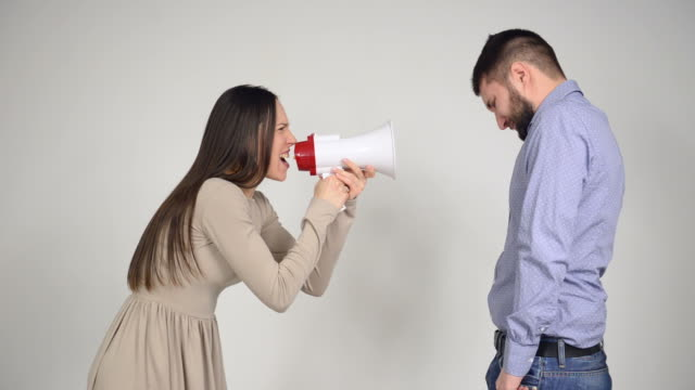 Wife using a megaphone to scream at husband