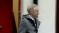 WikiLeaks founder Julian Assange leaving house ENGLAND London EXT Close shot number 7 on red door / Unidentified man with camera leaving / Julian...
