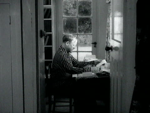William Golding works at his desk in his home near Salisbury