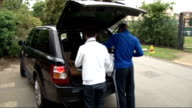 Andy Murray arrives ENGLAND London Wimbledon EXT Andy Murray standing at rear of car with unidentified man / Murray taking bags out of vehicle and...