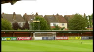 Kingsmeadow stadium Close up goalposts with netting tied up / GVs substitutes bench / Houses PULL OUT to pitch and stadium / Wide shot of pitch and...