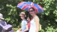 Wins for Johanna Konta and Andy Murray ENGLAND London Wimbledon All England Lawn Tennis Club EXT Woman in Wimbledon queue with Union Jack umbrella