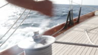 CU winch being turned on yacht which is racing through the sea.