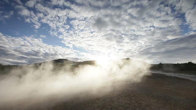 Wind blowing steam in front of sun.