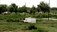 Wind blows through tall grasses around a camp trailer. Available in HD.