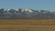 Wind farm turbines spin on snowy Abajo Mountains Monticello Utah