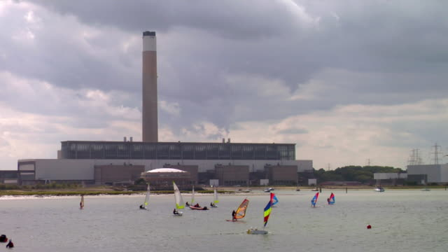 WS Wind surfers and boats on harbor, industrial building in background, Southampton, Hampshire, United Kingdom