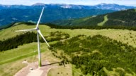 Wind turbine in the alps - static aerial view - source file cinema dng