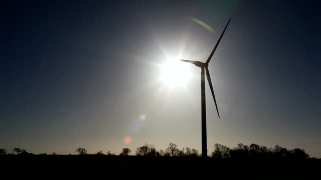 Wind Turbine Silhouette with sun and lens flare
