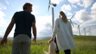 Wind turbines create electrical energy above couple in meadow, mountains