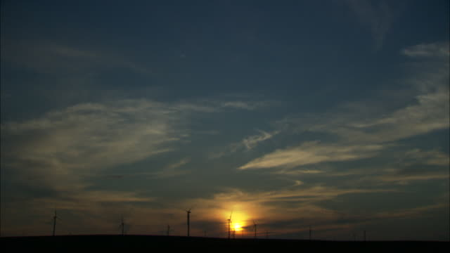 LS WS Wind turbines silhouetted against sunset sky, Huitengxile, Inner Mongolia, China
