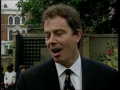Brixton Sudborne Primary School Ext TBV Tony Blair across playground during visit to school and up to wife Cherie Parents clapping Tony Blair intvw...