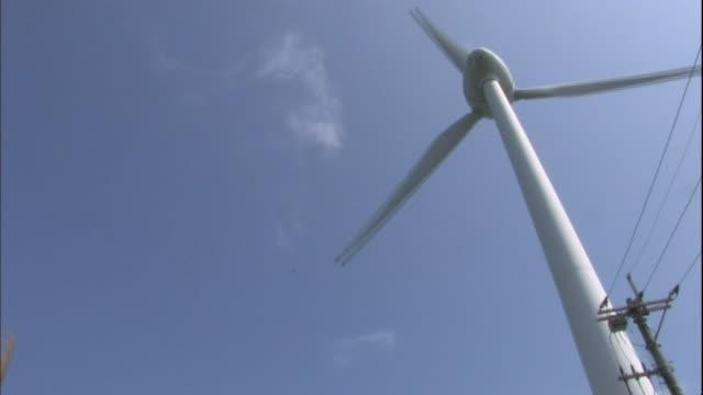 A windmill operates above a grassy field.