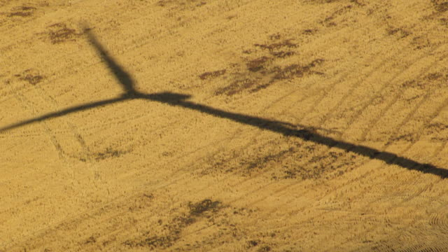 MS AERIAL Windmill shadow and windmill in wheat field wind farm / Oregon, United States