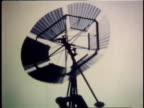 1978 MONTAGE windmill turning, man driving wagon / United States