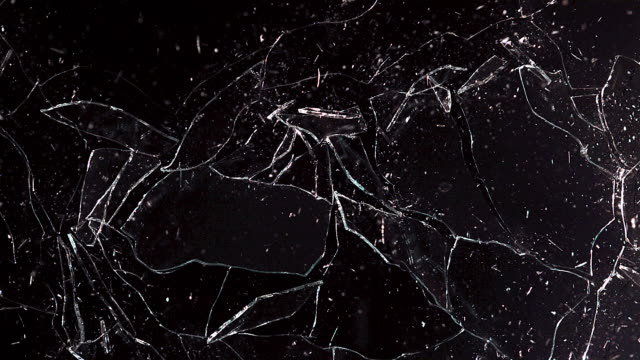Window pane shattering and  falling against black background, slow motion