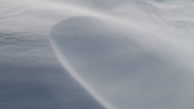 Winds blow over a snow drift.