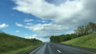 Windshield View of Highway Driving and White Clouds