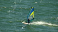 MS AERIAL TS Windsurfer surfing on Columbia River in strong changing sunlight / Oregon, United States