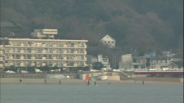 Windsurfers glide across the water in Sagami Bay near Zushi, Japan.