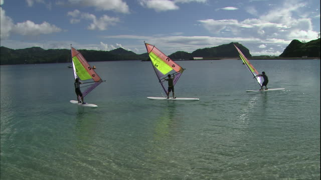Windsurfers sail on the Pacific Ocean off Chichijima Island in Japan.