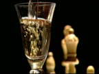 Wine glass being filled in front of white chess pieces