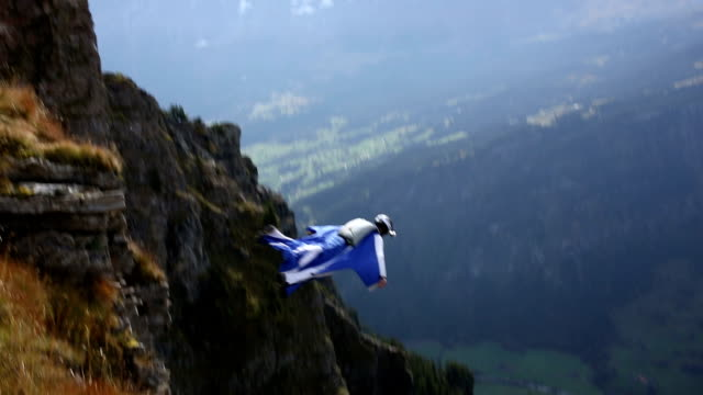 Wing suit flier descends from cliff to valley below