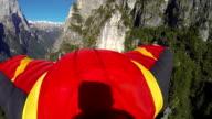 Wing suit flier descends from mountain cliff