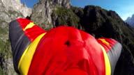 Wing-suit flier verläuft von mountain cliff