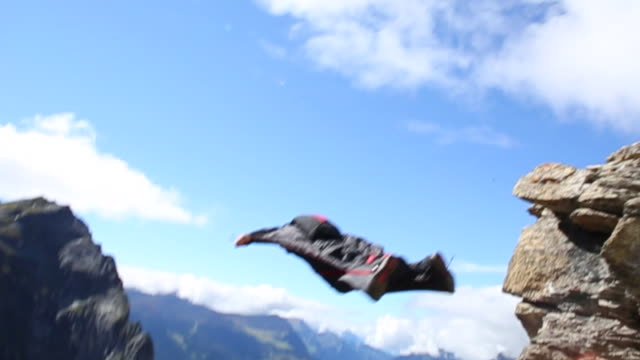 Wing suit flier jumps from cliff, soars above valley below