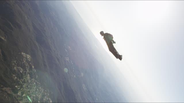 Wing suit pilot flies over hills